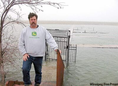 Blair Olafson inspects his docks at Narrows West Lodge, flooded from the rising Lake Manitoba waters.