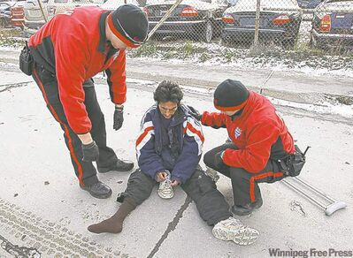 Downtown Watch officers Dustin Schollenberg and Wraylynn Black arrive to help Benny Meeseewaypetung off the street. The officers found and poured out a bottle of solvent carried by Meeseewaypetung, who a few years ago published a small  anthology of poems about love gone wrong.
