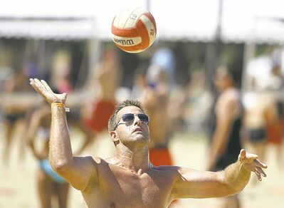 Former Winnipeg Blue Bomber, Doug Brown serves the ball for his newest team, Blue and Old, under sunny skies at the Super Spike Volleyball Tournament Saturday.