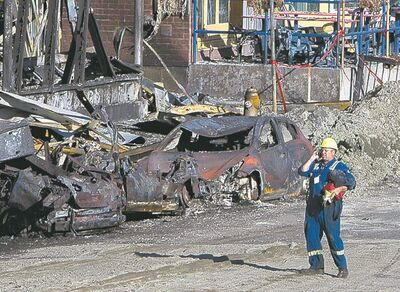 A worker walks through the crash site Thursday in Lac-Mégantic, Que., where a train derailed and ignited tanker cars carrying crude oil.