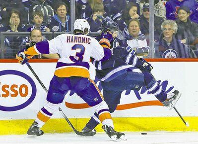 Islanders defenceman Travis Hamonic slows down Winnipeg forward Bryan Little  during second-period action at the MTS Centre Tuesday.