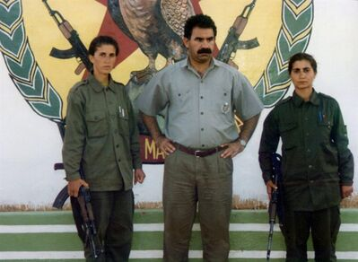 """In this early 1990s file photo, Sakine Cansiz, one of the founders of a militant group battling Turkish troops since 1984, left, and another woman surround Abdullah Ocaln, leader of the Kurdistan Workers Party, or PKK, at the Mahzun Korkmaz rebel camp in the Bekaa Valley, Lebanon. Cansiz and two other women were """"executed"""" at a Kurdish center in Paris, Thursday, Jan. 10, 2013. It was not immediately clear who killed the women, who belonged to the PKK, a group that Turkey and its Western allies, including the United States and the European Union, consider a terrorist organization. (AP Photo/IHA,) TURKEY OUT - INTERNET OUT"""