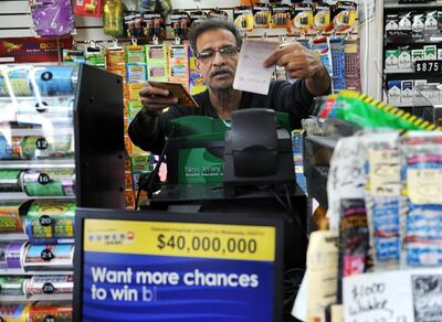 Baiju Amin hands lottery tickets to a customer at Union Food Store in Totowa, N.J. on Sunday, March 24, 2013. The lone winning ticket for a $338.3 million Powerball drawing was sold in New Jersey. Details on where and when the winning ticket was purchased and other related information were not disclosed Sunday by New Jersey Lottery officials, who also would not say if anyone claiming to hold the ticket had contacted them as of Sunday afternoon. (AP Photo/The Record (Bergen County NJ), Tyson Trish)