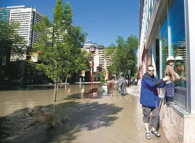nathan denette / the canadian pressMike Boonstra (left) helps his son Aden Boonstra along a wall as they walk through a flooded Chinatown in downtown Calgary,