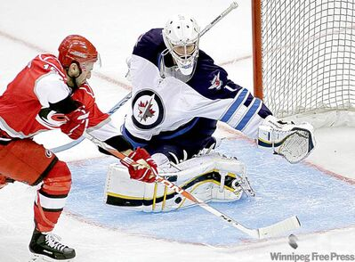 Carolina Hurricanes' Jon Matsumoto tries but fails to get a shot past Winnipeg Jets goalie David Aebischer during the third period Sunday.
