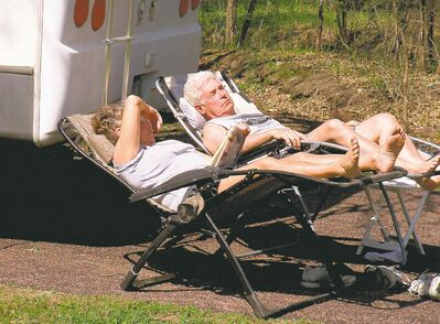 Patricia Zwart of Larchwood, Iowa, reads a book while her husband relaxes next to their camper in Palisades State Park in South Dakota near the Minnesota border.