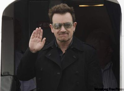 U2 frontman Bono waves as he gets off the U2 360 tour plane Friday at the Esso Avitat airport. U2 is performing at Canad Inns Stadium Sunday night.