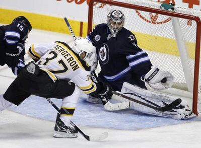 Winnipeg Jets goaltender Ondrej Pavelec (31) makes a save as Boston Bruins' Patrice Bergeron (37) and Jets' Tanner Glass (15) battle in front of the net during third-period NHL hockey action in Winnipeg Friday.