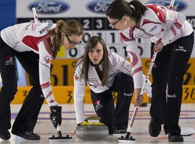 Canada's Rachel Homan releases a rock as Alison Kreviazuk (left) and Lisa Weagle sweep against the United States at the world women's curling championship in Riga, Latvia on Monday. The United States won 5-4.