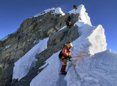 Climbers navigate the knife-edge ridge just below the Hillary Step on their way to the summit of Mount Everest in Nepal.
