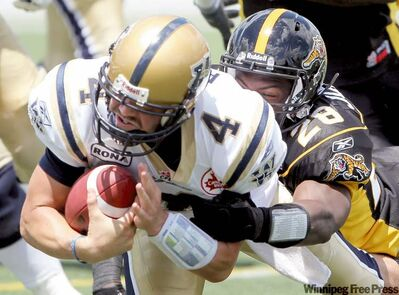 Bombers starting quarterback Buck Pierce is sacked by Hamilton's Jamall Johnson in the first half Sunday at Ivor Wynne Stadium.