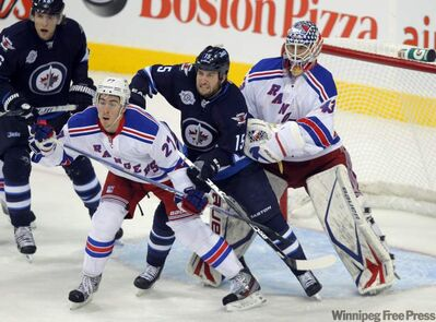 Tanner Glass gets in between some Rangers in front of the Ranger net Monday night at the MTS Centre.