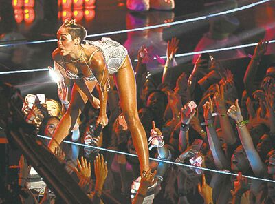 FILE - In this Aug. 25, 2013 file photo, Miley Cyrus performs at the MTV Video Music Awards at the Barclays Center in New York. From her twerk-a-thon at awards shows to her nearly nude poses to that now infamous tongue, we saw too many different sides (not to mention the backside) of the former teen queen. (Photo by Charles Sykes/Invision/AP, File)