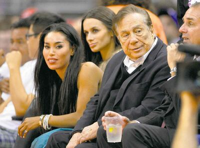 Los Angeles Clippers owner Donald Sterling and V. Stiviano, left, take in a Clippers game against the the Sacramento Kings last fall. Sterling is being accused of discouraging Stiviano from associating with blacks.