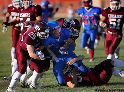 A crush of St. Paul's Crusaders drop Churchill Bulldogs' Matthew Miles (1) on his own goal line Thursday