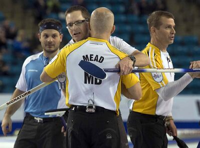 Manitoba's Jon Mead is congratulated by Quebec's Eric Sylvain along with Philippe Menard, left, and Manitoba skip Jeff Stoughton, right, at the Tim Hortons Brier in Kamloops, B.C. on Sunday. Manitoba won 9-5 and receives the bronze medal.