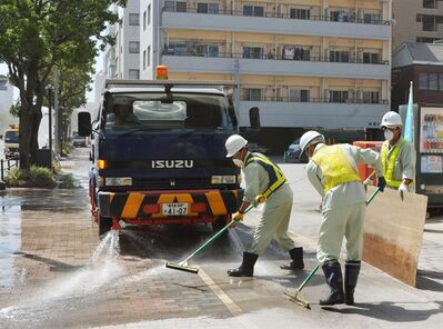 City officials wearing masks clean the pavement covered by ash Monday morning, Aug. 19, 2013 after the Sakurajima volcano erupted Sunday afternoon in Kagoshima, on the southern Japanese main island of Kyushu. People in the city wore masks and raincoats and used umbrellas to shield themselves from the ash after the eruption. (AP Photo/Kyodo News) JAPAN OUT, MANDATORY CREDIT