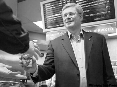 Prime Minister Stephen Harper hands out the brew at a Tim Hortons during a campaign stop in Dieppe, N.B. Friday.