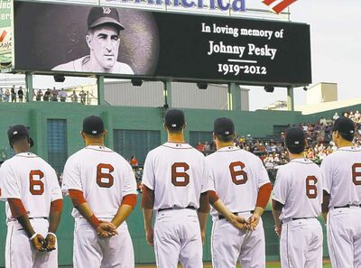 Boston Red Sox players, all wearing No. 6 jerseys, line up on the field at Fenway Park to honor the late Johnny Pesky, prior to a baseball game against the Los Angeles Angels in Boston Tuesday, Aug. 21, 2012. Pesky, who played, managed and served as a broadcaster for the Red Sox in a baseball career that lasted more than 60 years, died last week. He was 92. (AP Photo/Elise Amendola)