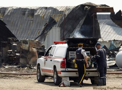 A fire investigator on the scene of a fire that gutted the length an empty hog barn near Notre Dame de Lourdes in June. The farm  had recently been at the centre of a large animal-cruelty investigation.