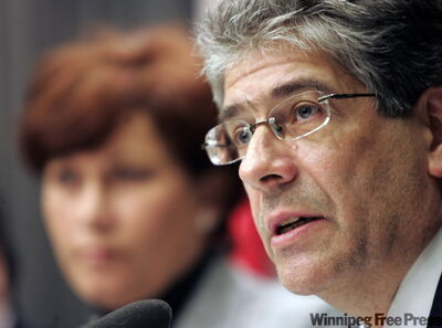 Joel Kettner, Manitoba's chief medical officer of health, speaks at a new conference at the Manitoba legislature on Thursday, with Health Minister Theresa Oswald in the background.