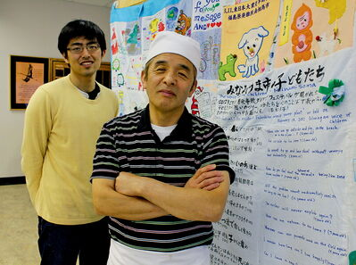 Sadao Ohno (centre) and Atsushi Kawazu with cloth letters sent overseas by Minamisoma Fukushima Mayor Sakurai-San and the city's young children. The letter is making its way across Canada.