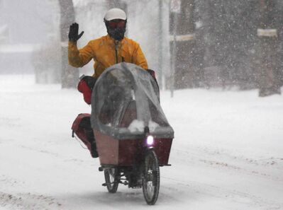 A man cycles through heavy snow on Grosvenor Avenue in River Heights Wednesday morning.