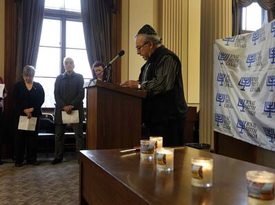 Roger Armbruster of Canada Awakening Ministries, reads names of Holocaust victims at the Manitoba Legislative Building Monday, as part of Holocaust Memorial Day.