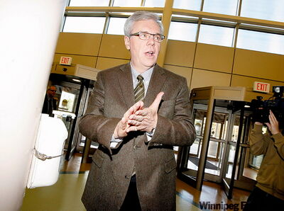 Premier Greg Selinger washes his hands with sanitizer as he visits St. Boniface General Hospital Wednesday.