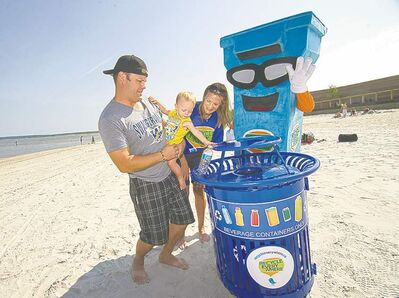 David Lipnowski / Winnipeg Free Press Xavier Lamb, 1, gets help from his parents Mike and Lauren to pop a plastic bottle into a new recycling bin Wednesday morning as the Recycle Everywhere mascot cheers him on.