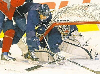 Jets goalie Ondrej Pavelec covers up while blue-liner Dustin Byfuglien (in red) and forward James Wright crash the net during Wednesday's practice at the MTS Centre. Winnipeg hosts Colorado tonight.