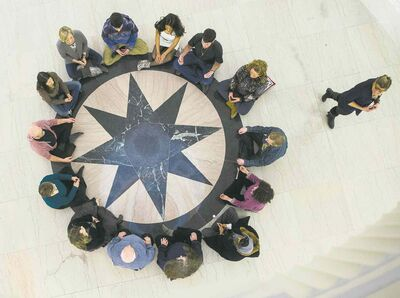 Fourteen people meditate around the Pool of the Black Star Friday evening at the Manitoba Legislative Building.