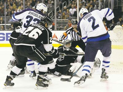 Los Angeles goalie Jonathan Quick blocks a shot from Winnipeg defenceman Adam Pardy while Dustin Byfuglien (33) looks for a rebound Saturday night.