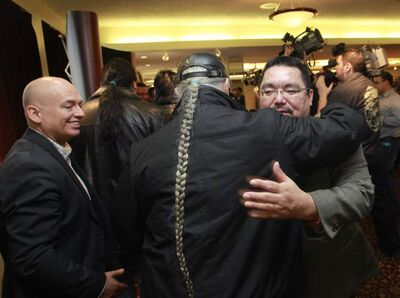 Chief Glenn Hudson (right) is embraced by Bill Traverse the AFN Regional Chiefs of Manitoba, along with lawyer Norman Boudreau (left) after the announcement of the recent federal court decision regarding Kapyong Barracks.