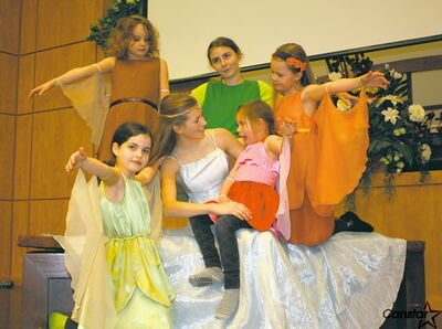 The fairies from A Midsummer Night's Dream surround their queen, Titania, as played by Hannah Beynon.