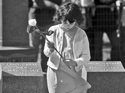 Andrew Vaughan / The Canadian PressA child holds a flower to place on a grave marker at the memorial service at Fairview Lawn Cemetery in Halifax Sunday.