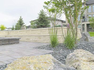 Granite boulders punctuate this sloping urban landscape without detracting from any of the other hardscaping elements. Perennial beds have been filled with crushed granite for both an aesthetic and practical purpose.