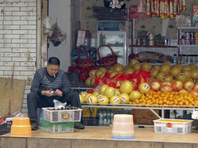 A shopkeeper enjoys a puff as he prepares fruit for sale in a storefront shop in Chengdu.