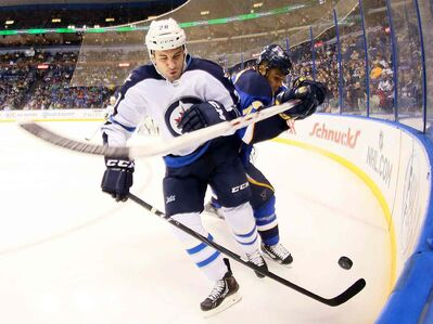 St. Louis Blues right-winger Ryan Reaves (right) and Winnipeg Jets centre Patrice Cormier battle for the puck in first-period action during an NHL game at the Scottrade Center in St. Louis Monday.