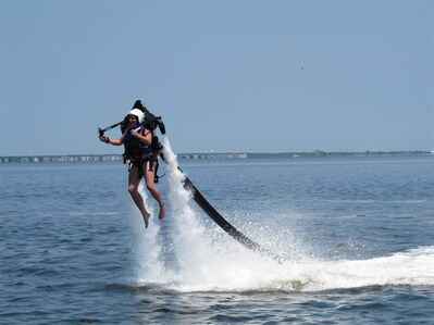 In this photo taken July 12, 2012, Jenna Lee of Brick Township, N.J., rises above the water of Barnegat Bay in Berkeley Township, N.J., while using a JetLev propulsion device. The device resembles a backpack with handles and two powerful jet nozzles, connected by a long black hose to a 10-foot boat that trails behind the user in the water and forces water through the hose and out the nozzles, creating the lift that propels the wearer into the air. (AP Photo/Wayne Parry)