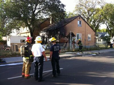 Firefighters at the scene of a house fire Sunday at the corner of Machray Avenue and Salter Street.