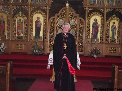 Rt. Rev. Msgr. Michael Buyachok stands in front of the elaborate iconostasis with icons written by Sviatoslaw Hordynsky.