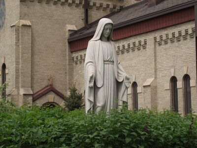 A statue of Mary stands outside St. Mary's Roman Catholic Cathedral, amid the bustle of Winnipeg's downtown.     Mary outside the cathedral