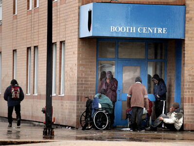 A group of homeless people huddle for shelter under the Booth Center's Canopy Monday afternoon seeking shelter from the rain.