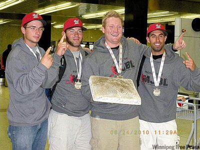 Left-fielder Darryl Ellis, catcher Brett Schreyer, manager Jamie Bettens and shortstop Wes Pomarensky (from left) whoop it up upon arrival home at Winnipeg airport on Tuesday.