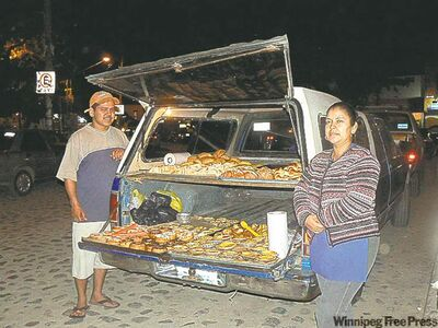 "Betty Cambrano, right, and Gabriel Lopez run ""Bakery Jolanda,'' from the back of their station wagon parked on the main street in Sayulita, Mexico. They specialize in homemade fruit empanadas."