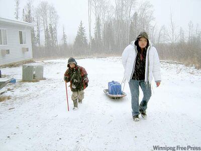 Nicole Mason, 14, and her brother haul water to their trailer at St. Theresa Point last winter. More than 1,400 homes on northern reserves lack running water.