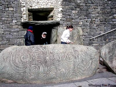 An intricately carved rock guards the  entrance to  Newgrange.