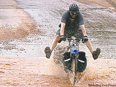 Calgary's Darren Flach rides through a swollen river near Santa Barbara.