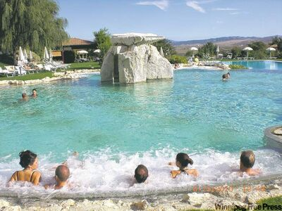 Bathers relax on one of the bubbling massage beds in the outdoor thermal pool.